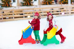 Kids ice skating in winter. Ice skates for child. Kids ice skating in winter park rink. Children ice skate on Christmas fair. Little girl and boy with skates on stock photos
