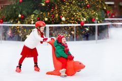 Kids ice skating in winter park rink. Children ice skate on Christmas fair. Little girl and boy with skates on cold day. Snow. Outdoor fun for child. Winter royalty free stock photos