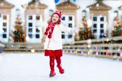 Kids ice skating in winter. Ice skates for child. Kids ice skating in winter park rink. Children ice skate on Christmas fair. Little girl with skates on cold stock photo