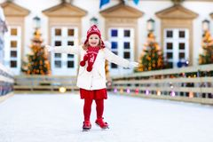 Kids ice skating in winter. Ice skates for child. Kids ice skating in winter park rink. Children ice skate on Christmas fair. Little girl with skates on cold Stock Photography