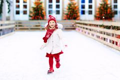 Kids ice skating in winter. Ice skates for child. Kids ice skating in winter park rink. Children ice skate on Christmas fair. Little girl with skates on cold stock photos