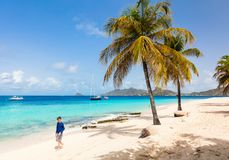 Idyllic beach at Caribbean. Kids at idyllic tropical beach with white sand, palm trees and turquoise Caribbean sea water on Mayreau island in St Vincent and the stock image