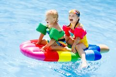 Kids on inflatable float in swimming pool. Royalty Free Stock Photos