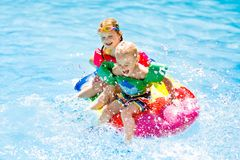 Kids on inflatable float in swimming pool. Boy and girl on inflatable ice cream float in outdoor swimming pool of tropical resort. Summer vacation with kids Royalty Free Stock Photography