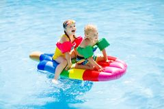 Kids on inflatable float in swimming pool. Boy and girl on inflatable ice cream float in outdoor swimming pool of tropical resort. Summer vacation with kids Royalty Free Stock Photos