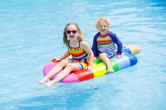Kids on inflatable float in swimming pool. Boy and girl on inflatable ice cream float in outdoor swimming pool of tropical resort. Summer vacation with kids Stock Images