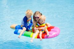 Kids on inflatable float in swimming pool. Stock Images