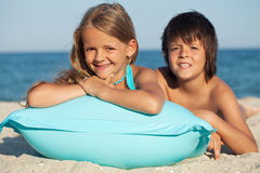 Kids with inflatable raft at the beach Stock Photography