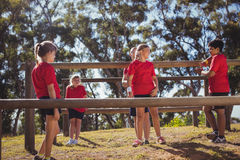 Kids interacting with each other during obstacle course training. In the boot camp Stock Image