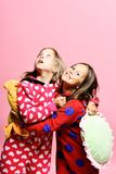 Kids with interested and happy faces hold pillows. Kids with interested and happy faces hold green and yellow sun pillows. Friends in pink pajamas isolated on royalty free stock image