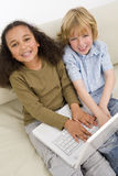Kids On The Internet. Two young children having fun on a laptop while sitting on a settee Stock Image