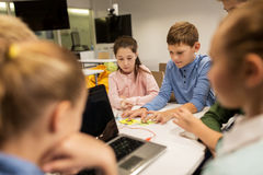 Kids with invention kit at robotics school. Education, children, technology, science and people concept - group of happy kids with laptop computer playing and Stock Photos