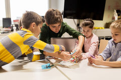 Kids with invention kit at robotics school. Education, children, technology, science and people concept - group of happy kids with laptop computer playing and Royalty Free Stock Images