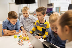 Kids with invention kit at robotics school. Education, children, technology, science and people concept - group of happy kids with laptop computer playing and royalty free stock photo