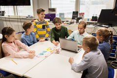 Kids with invention kit at robotics school. Education, children, technology, science and people concept - group of happy kids with laptop computer playing and Royalty Free Stock Photography