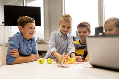 Kids with invention kit at robotics school. Education, children, technology, science and people concept - group of happy kids with laptop computer playing and Stock Photography