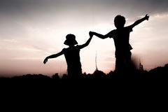 Kids jump off a hill raising hands up high. Silhouettes of children jumping off a cliff at sunset. Boy and girl jump high holding hands. Brother and sister Stock Images