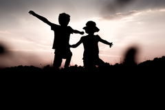 Kids jump off a hill raising hands up high. Silhouettes of children jumping off a hill at sunset. Little boy and girl jump raising hands up high. Brother and stock photo