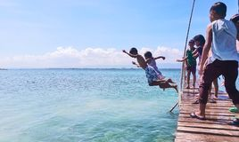 Kids jump on pair on a footbridge in a resort in Olango, taken on March 2018. Happy kids jumping on a footbridge at a resort in Olango Island, where they are Royalty Free Stock Photo