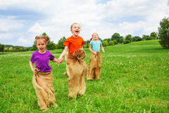 Kids jump in sacks on a grass. Kids jump in sacks on a meadow with dandelions Stock Photos