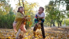 Kids jump and throw yellow leaves on background of trees and foliage at autumn park in sunlight. Kids jump and throw yellow leaves on background of trees and stock video