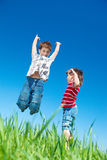 Kids jumping. Happy kids jumping in grass royalty free stock photography