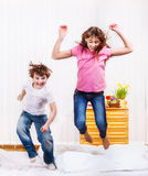Kids jumping. Cheerful kids jumping on the bed Stock Photo