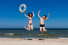 Kids jumping on beach Stock Images