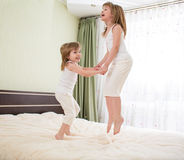 Kids jumping on bed Stock Photo