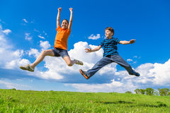Kids jumping on green hills. Happy kids jumping on green hills against blue sky Stock Image