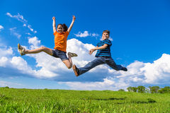 Kids jumping on green hills. Happy kids jumping on green hills against blue sky Stock Photos
