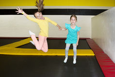 Kids Jumping on Indoor Trampolines. Two little girls having fun jumping on an indoor trampoline Stock Photos