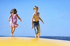 Kids jumping on an inflatable trampoline. A boy and a girl playing together on an inflatable trampoline stock photos