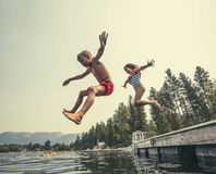Kids jumping off the dock into a beautiful mountain lake. A little boy and little girl jumping off the dock into a beautiful mountain lake. Having fun on a