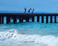 Kids Jumping off Pier Into Ocean in Puerto Rico Stock Photography