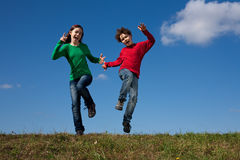 Kids jumping outdoor. Kids jumping against blue sky Stock Photography