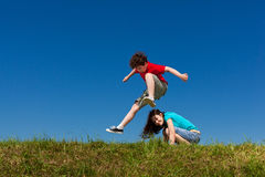 Kids jumping outdoor. Kids jumping against blue sky Royalty Free Stock Image