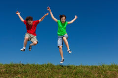 Kids jumping outdoor stock photo