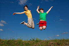 Kids jumping outdoor stock images