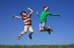 Kids jumping outdoor. Kids jumping against blue sky Stock Photos