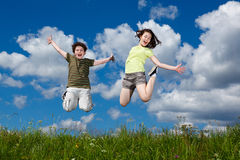 Kids jumping outdoor. Kids jumping against blue sky Stock Images