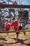 Kids jumping over the hurdles during obstacle course training. In the boot camp Royalty Free Stock Photography