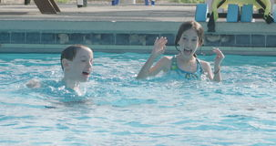 Kids jumping and playing in a swimming pool stock footage