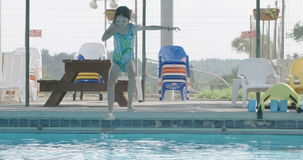 Kids jumping and playing in a swimming pool stock video footage