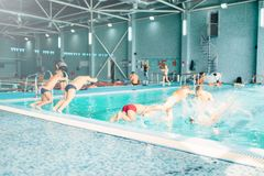 Kids jumping into pool with clean blue water. View from back. Children learn to swim and dive. Modern sports center on background. Sportive kids activity Royalty Free Stock Photo