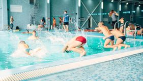 Kids jumping into pool with clean blue water. View from back. Children learn to swim and dive. Modern sports center on background. Sportive kids activity Stock Images