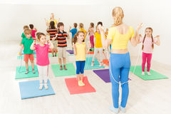 Kids jumping ropes with gymnastic coach in gym stock photography