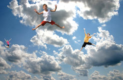 Kids Jumping in the Sky. On top of clouds royalty free stock images