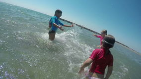 Kids jumping and splashing in the sea stock video footage