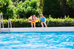 Kids jumping into swimming pool Stock Photos